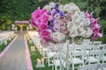 Ceremony flower arrangement on top of Lucite stand, purple orchid, purple rose, purple lisianthus