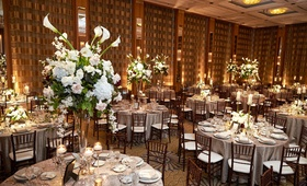 tall flower centerpiece greenery white flower calla lily on glass stands on silver tablescapes
