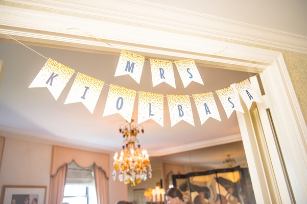 Mrs. paper banner hung up in hotel suite while bride and bridesmaids get ready for wedding