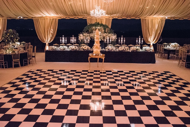 Wedding reception tent event with tall cake and black white checkerboard dance floor vinyl black