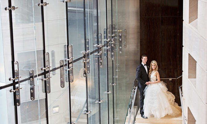 Bride in Vera Wang wedding dress with groom in tuxedo before wedding at rooftop terrace for theater