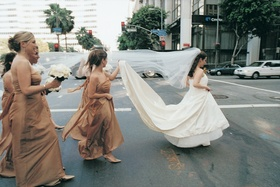 Bridesmaids and bride in city crosswalk