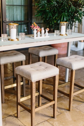 white cocktail table with tufted nail head bar stools wood legs, gold candle votives, pink orchids