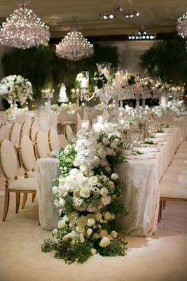 wedding reception long table with gold chairs overflowing flower runner white orchid rose greenery
