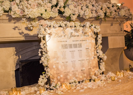 seating chart with clever table names, frame full of flowers