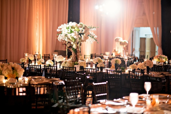 black and white décor, white and green floral arrangements branch risers lighting
