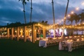 wood structure string lights outdoor wedding reception evening dusk long tables vineyard chairs