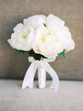 Bride's bouquet with white peony flowers wrapped with satin ribbon