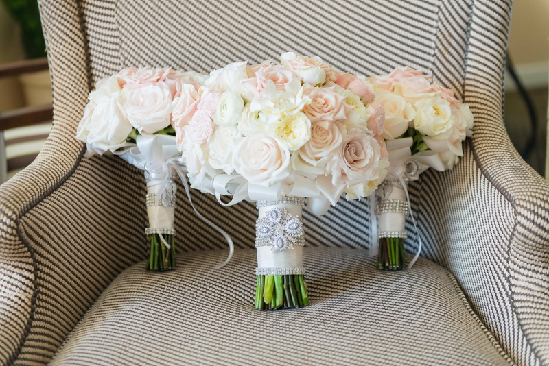 White and light pink rose bouquets for bride and bridesmaids on arm chair with crystal wraps