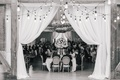 Black and white photo of guests enjoying reception drapery flower chandelier patio string lights