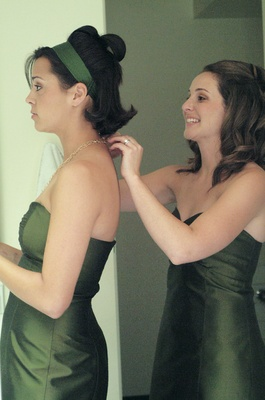 Getting ready shot of bridesmaids in green dresses