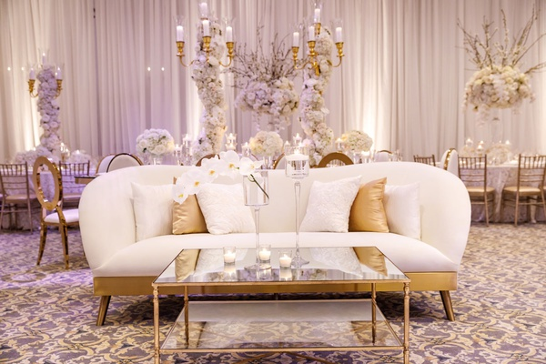 wedding reception lounge seating area white gold sofa curved gold mirror coffee table candles orchid