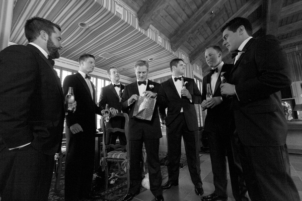 Black and white photo of groom opening wedding gift