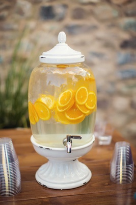 White distressed drink dispenser with silver spout and ice water filled with orange slices