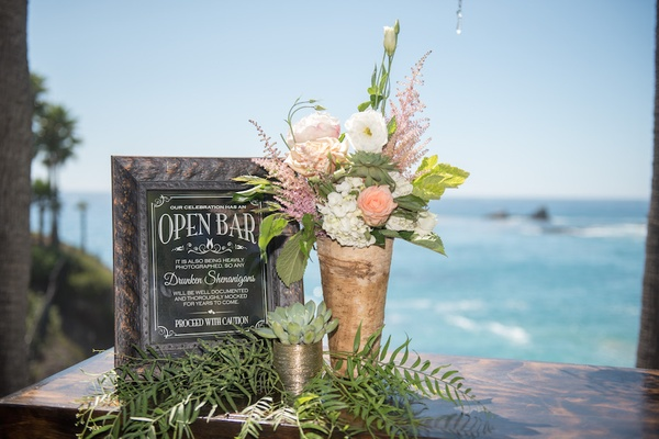 Oceanfront wedding reception bar sign in copper frame, white hydrangeas, lisianthus, peach roses