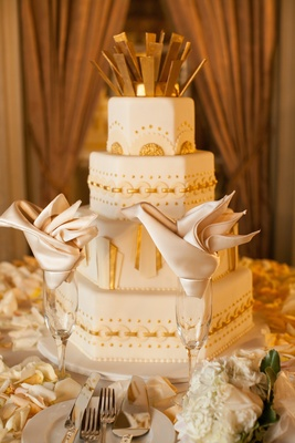 White wedding cake with hexagon shaped tiers and gold embellishments