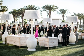 Outdoor cocktail hour with large heat lamps that look like lamp shades, wood furniture whitewash