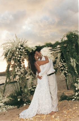 bride and groom kiss in front of chuppah decorated with greenery and white flowers
