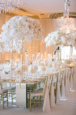 opulent wedding reception with ivory and gold, floral arrangements on tall gold stands, chandeliers