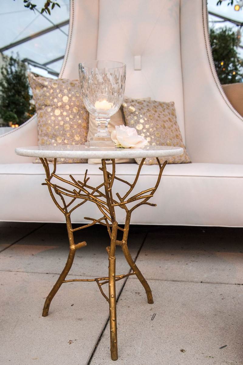 Accent table with gold branches at base around white settee at cocktail hour