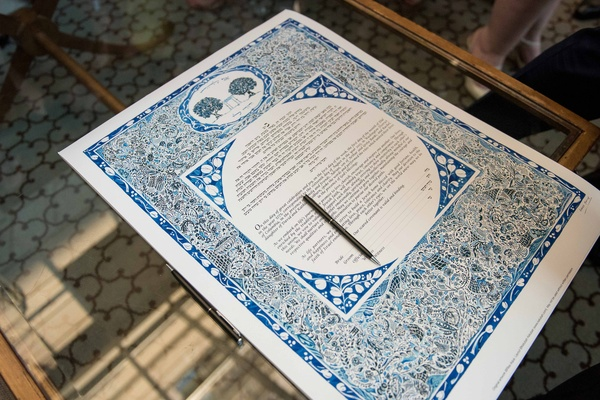 a traditional jewish ketubah with blue details and a floral design