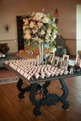 escort cards with large floral centerpiece with blush roses, dusty miller, and eucalyptus