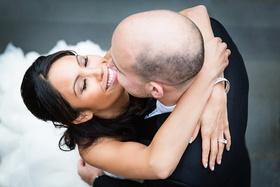 Happy bride in Lazaro gown hugs groom in black tuxedo