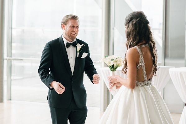 Groom in tuxedo bow tie and calla lily boutonniere reaction to bride in first look crystal back open
