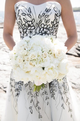 Bride in black and white dress holds all-white bouquet