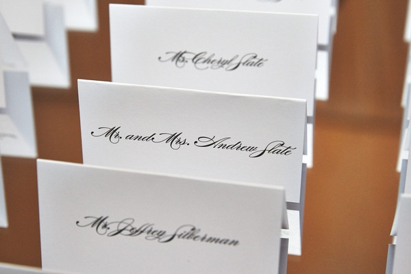 White seating cards with black script font names