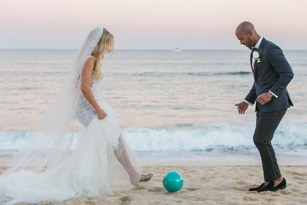 a bride and groom kick a soccer ball around on the beach after their wedding
