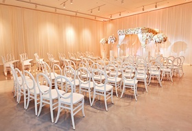 wedding ceremony seats white cushionless round back cahirs, peach uplighting