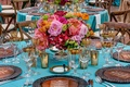 Wedding reception centerpiece with pink, orange and green flowers on turquoise tablecloth