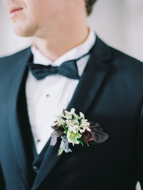 Groom in a three-piece black tuxedo suit, boutonniere of small white flowers, purple leaves, verdure