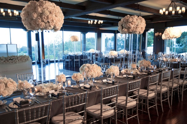 Long wedding reception table floor to ceiling windows white flower arrangements high and low lucite
