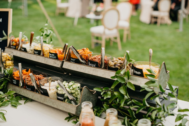 outdoor wedding reception garden party salad bar with bacon, cheddar cheese, and more in glass jars