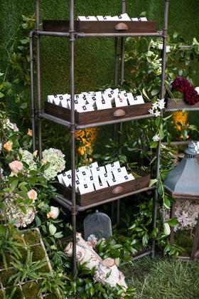 wedding reception escort cards in wood tray on industrial book shelf hedge wall fall flowers green