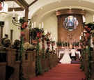 Wedding ceremony aisle decorated with tall candelabra covered in greenery and topped with flowers