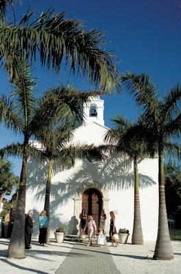 Palm trees outside white church on beach