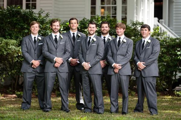 groom and groomsmen in dark grey suits from men's wearhouse