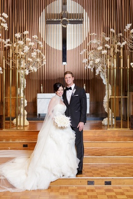 bride in lazaro ball gown with tulle cape, groom in tuxedo, in front of christian altar