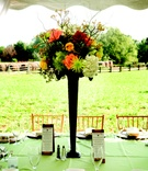 Wedding reception centerpiece of orange, green, white, yellow, and red flowers