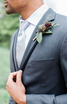 boutonniere with dark burgundy blooms and green leaves