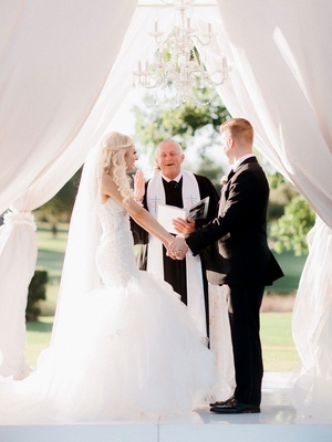 Bride in strapless trumpet gown with groom holding hands during outside ceremony Christian wedding