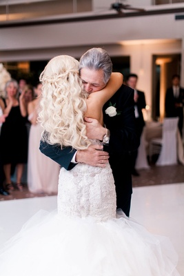 Father of bride in suit with white boutonniere hugging bride on dance floor long blonde hair
