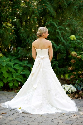 Bride in a strapless Vera Wang dress with embroidered lace, sash, updo at Lake Geneva Country Club