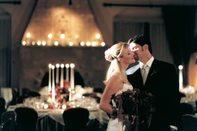 Bride and groom kiss in reception ballroom