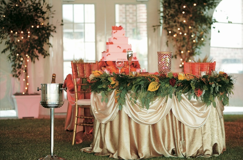 Gold linen covered couple's table with greenery and fall leaves