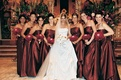 Bridesmaids wearing long red dresses and holding rose bouquets