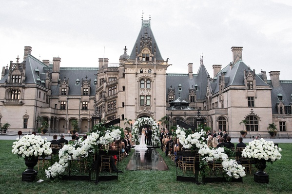 Wedding ceremony with black wrought iron gates, white flowers, black aisle runner outdoors castle